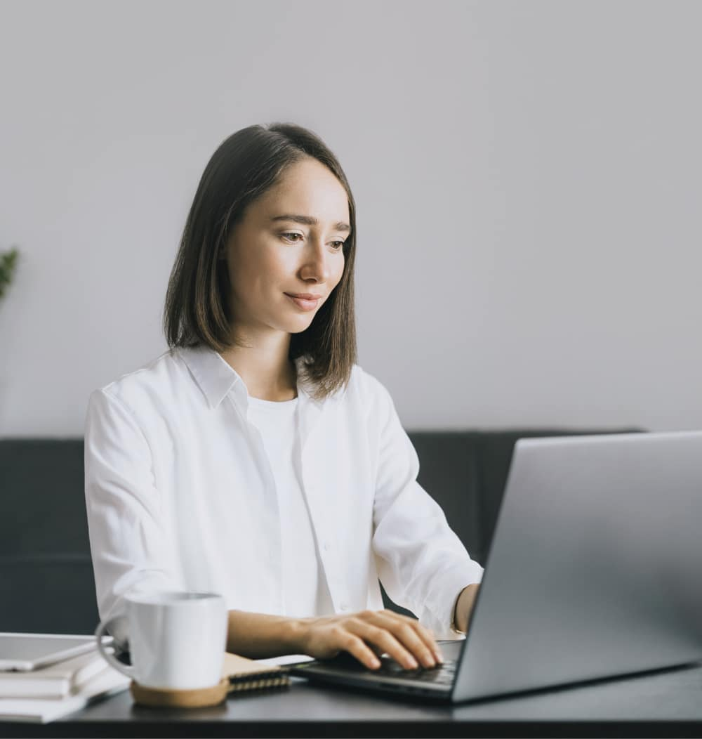 young woman sitting at a desk using her laptop to work